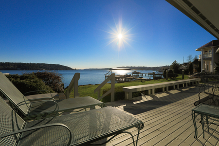 waterfront property: Beautiful sunset view from large deck of waterfront home with Wrought Iron Chaise Lounge. Northwest, USA