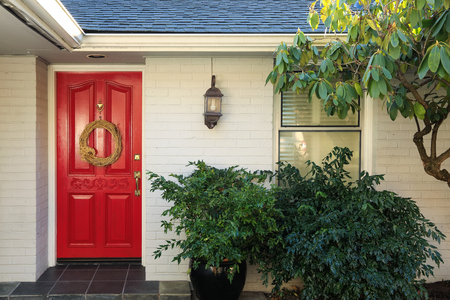 front porch: Front porch with white painted brick exterior, red entrance door accented with Door Wreath and finished with pot planter under wall lantern. Northwest, USA