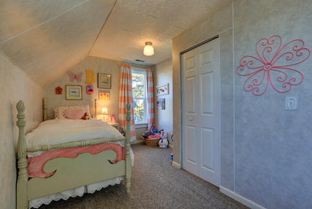 photo: Pink and green girls attic bedroom with sloped ceiling over poster bed and small window dressed in pink stripe curtains. Northwest, USA Stock Photo