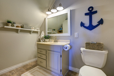powder room: Marine style powder room interior in soft tones features vaulted ceiling over creamy white single bathroom vanity and toilet. Northwest, USA Stock Photo