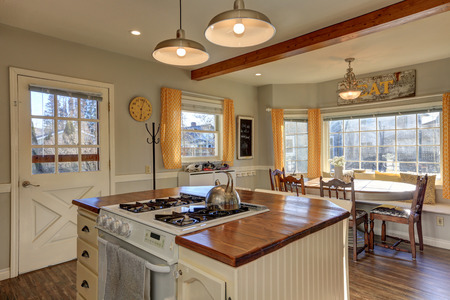 renovated: Newly renovated Kitchen and breakfast nook  boasts wood beams on ceiling, pale grey walls, white island with wood counter top and hardwood floor. Northwest, USA
