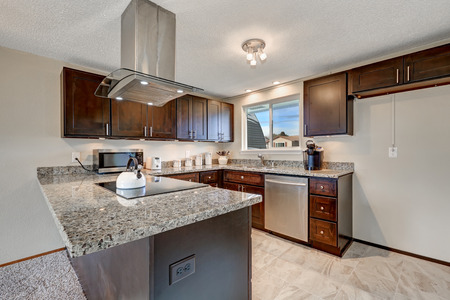 renovated: Newly renovated kitchen boasts dark wood cabinets with granite counter tops, contemporary steel hood on the ceiling and tile floor. Northwest, USA Stock Photo