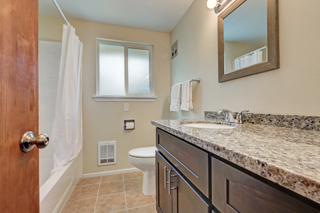 renovated: Renovated bathroom interior with creamy walls, dark wood bathroom vanity topped with granite counter and tub and shower combination. Northwest, USA Stock Photo