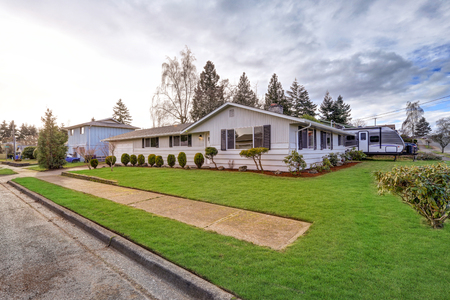 rambler: Charming Updated rambler features a white painted siding exterior accented with windows finished with dark gray shutters. Northwest, USA Stock Photo