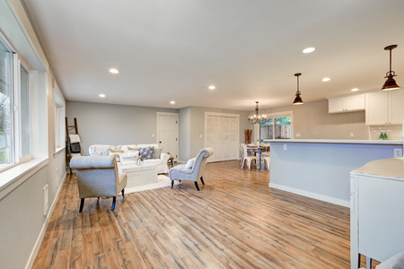 Airy light filled living room in soft blue and grey colors. Open floor plan interior features comfortable sofa with chairs, breakfast nook and kitchen. Northwest, USA