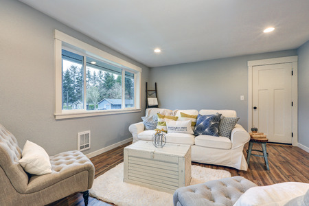northwest: Cozy living room space with soft blue grey walls, furnished with tufted chairs, slipcovered white sofa with colorful pillows and white painted trunk as a coffee table over fluffy rug. Northwest, USA