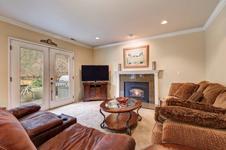 Family room design in brown and beige tones with tan walls paint color, fireplace with granite surround and brown sofa facing oval cocktail table and glass doors to patio. Northwest, USA