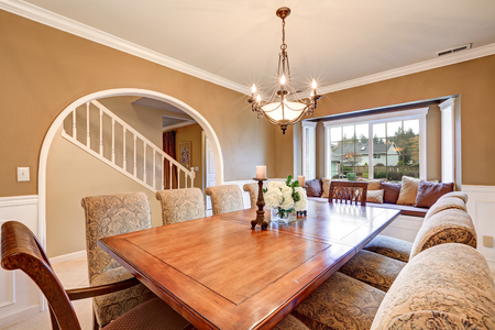 upholstered: Elegant interior design of formal dining room with tan walls, wainscoting, arched doorway, window seat and large dining table with upholstered chairs. Northwest, USA