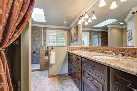 Vers verbouwde badkamer met prachtige dubbele wastafels, geaccentueerd met donkere kasten, granieten toonbanken en mozaïek backsplash, en dakraam boven bubbelbad en inloopdouche. Northwest, VS.