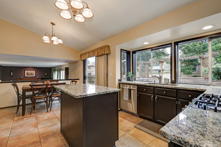 renovated: Classic Kitchen room design with kitchen island, dark wood cabinets topped with glossy granite counters, stainless steel appliances and tile floor. Northwest, USA