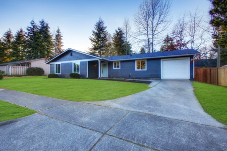 Craftsman blue one-story low-pitched roof home in Tacoma. Well kept front yard with green lawn . Northwest, USA