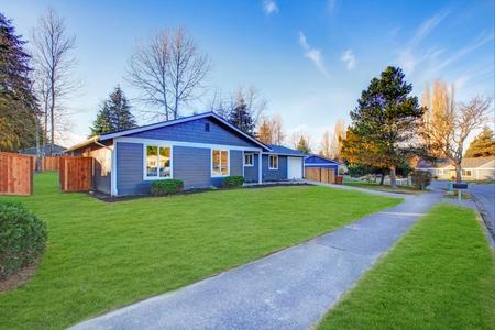 Vakman blauw een-laag laag dak huis in Tacoma. Goed onderhouden voortuin met groen gazon. Northwest, VS.