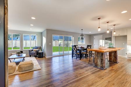 Open plattegrond interieur met gepolijste hardhouten vloeren toont een indrukwekkend gerecycled hout keuken eiland, zwarte eettafel set en schuifdeuren naar omheinde achtertuin. Noordwest, Verenigde Staten