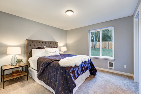 nightstands: Lovely master bedroom with soft grey walls, queen bed with tufted headboard and dressed in dark blue bedding and white faux fur throw blanket, and boasts reclaimed wood nightstands topped with lamps.