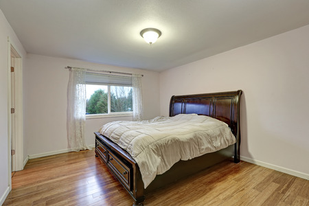 White bedroom with dark stained wood bed with lower drawers atop bamboo wood floors. Northwest, USA