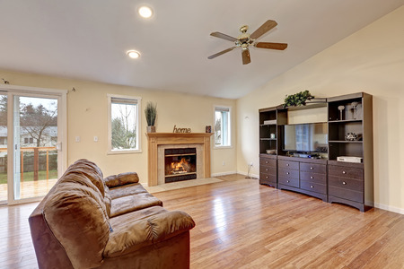 Spacious living room with tall vaulted ceiling over yellow beige walls framing traditional fireplace and dark wood media cabinet atop polished bamboo floors. Northwest, USA
