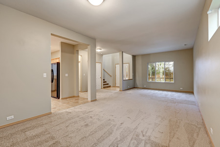 Empty beige interior of new contemporary home features wall to wall carpet flooring and staircase to upstairs floor. Northwest, USA Stock Photo