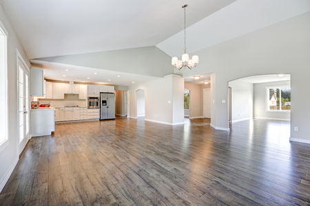 Spacious rambler home interior with vaulted ceiling over glossy laminate floor. Empty light filled dining or living space adjacent to new white kitchen room features pale grey walls. Northwest, USA Foto de archivo