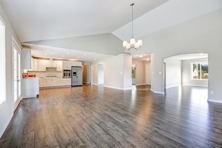 Ruim huisbinnenland van de wandelaar met gewelfd plafond over glanzende gelamineerde vloer. Lege, met licht gevulde eet- of woonruimte grenzend aan de nieuwe witte keukenruimte met lichtgrijze muren. Northwest, VS. Stockfoto - 72437173