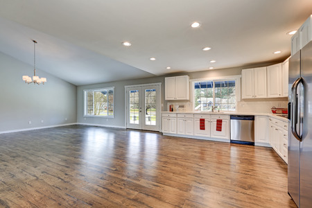 renovated: Spacious rambler home interior with vaulted ceiling over glossy laminate floor. Light filled kitchen room boasts white cabinets and stainless steel appliances. Northwest, USA Stock Photo