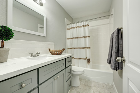 Het nieuwe badkamerinterieur heeft een zilvergrijze ijdelheidskast met een marmeren aanrechtblad en een witte spatrand. Northwest, VS.