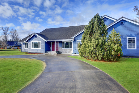 Beautiful rambler house with tile roof, blue siding, covered porch with double red front door and concrete driveway. Northwest, USA