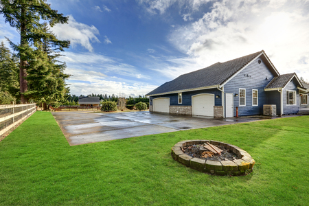 Backyard view of blue rambler home with three car attached garage, driveway, fire pit, well kept lawn and equestrian area at the back.  Northwest, USA Stock Photo