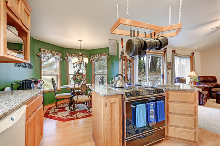kitchen island: Bright rambler kitchen boasts vaulted ceiling over bar style kitchen island with kitchen hanging rack above it, granite counters, mosaic backsplash and breakfast nook with green wall. Northwest, USA