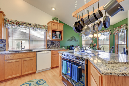 Bright rambler kitchen boasts vaulted ceiling over bar style kitchen island with kitchen hanging rack above it, granite counters, mosaic backsplash and breakfast nook with green wall. Northwest, USA