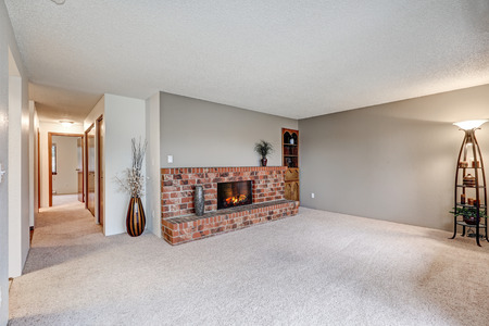 Empty living room next to hallway features grey walls, carpet floor and red brick fireplace. Northwest, USA