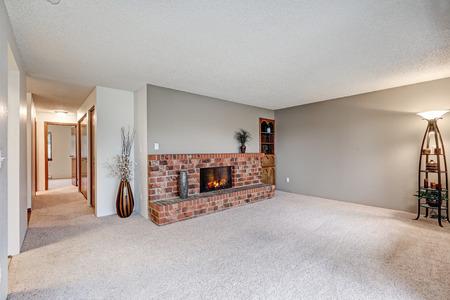 機能灰色の廊下の壁、カーペットの床、赤れんが造りの暖炉の横にある空のリビング ルーム。米国北西部