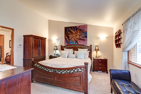 furniture design: Chic master bedroom features vaulted ceiling over gorgeous wood carved bed, cabinet, two nightstands and black leather tufted bench by the window. Northwest, USA