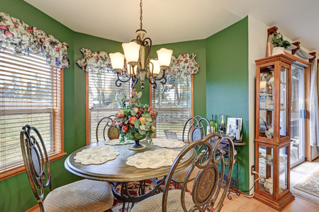 apartment: Amazing bright green breakfast nook boasts wrought iron table set lit by elegant chandelier, windows dressed in colorful curtains, small glass cupboard by the doors to backyard. Northwest, USA