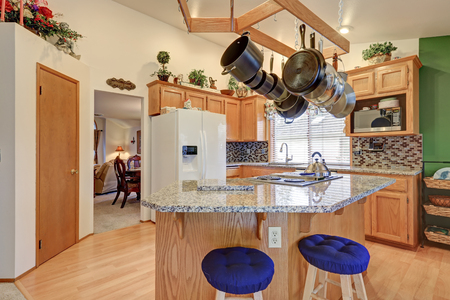 renovated: Bright rambler kitchen boasts vaulted ceiling over bar style kitchen island with kitchen hanging rack above it, wood cabinets with granite counter tops paired with mosaic backsplash. Northwest, USA