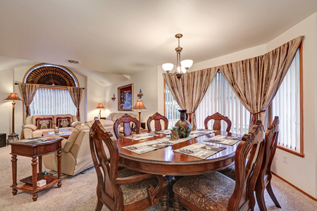 Beautiful formal dining and living room interior boasts elegant oval table lined by wood carved chairs. Cozy living space showcases beige leather sofas and high vaulted ceiling framing arched window.