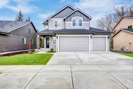 Grey house exterior with two garage spaces on a blue sky background. Northwest, USA