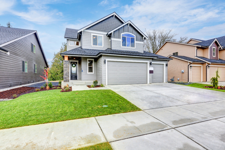 grey house: Grey house exterior with two garage spaces on a blue sky background. Northwest, USA