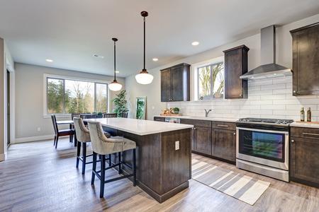 Nieuwe keuken met donkerhouten kasten, witte backsplash-metrotegel en een groter eiland met wit en grijs kwartsglas dat wordt verlicht door hanglampen. Northwest, VS. Stockfoto