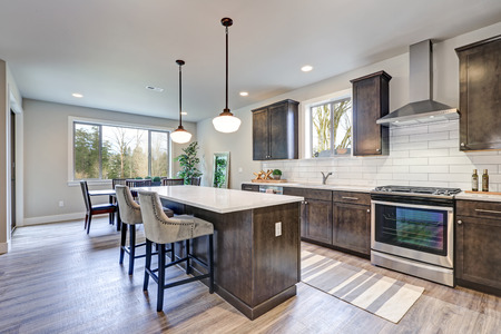 New kitchen boasts dark wood cabinets, white backsplash subway tile and over sized island with white and grey quartz counter illuminated by pendant lights. Northwest, USA