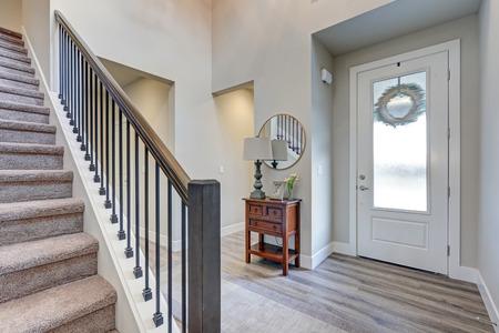 Grijze foyer met laminaatvloer, hoog plafond, ingericht met console tafel naast witte voordeur en trap met metalen en houten balustrades. Northwest, VS.
