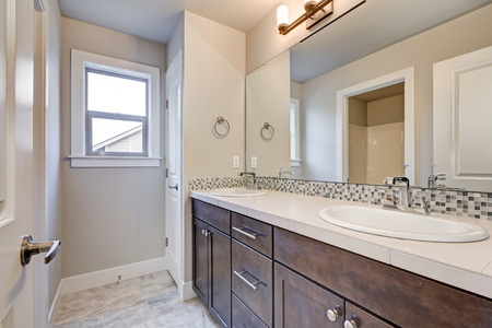 New light bathroom interior with double sink dark wood bathroom vanity accented with mosaic backsplash. Northwest, USA Stock Photo