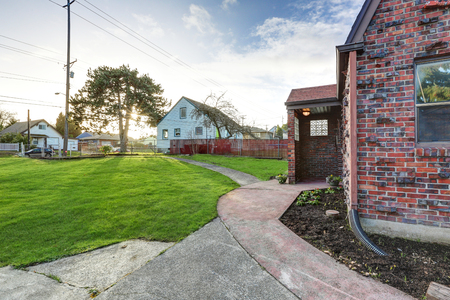 Small red brick home on a sunny day. View of covered front porch. Northwest, USA