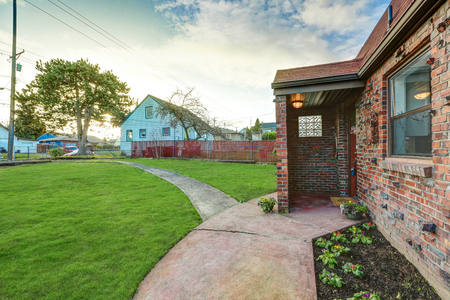 Small red brick home exterior on a sunny day. View of covered front porch. Northwest, USA