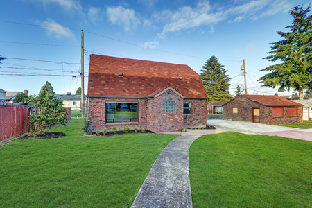 Small red brick home exterior with detached garage on a sunny day. Northwest, USA