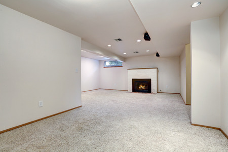 White empty basement room with fireplace and wall to wall carpet floor. Northwest, USA Stock Photo