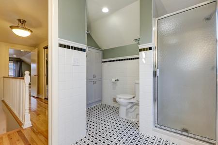 Bathroom features subway tiled half walls with black tile border over vintage black and white tile floor. Northwest, USA