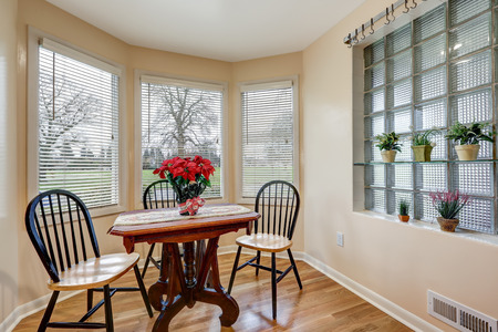Light filled breakfast nook with soft peach walls furnished with vintage pedestal table and round back chairs under transom windows over hardwood floor. Northwest, USA