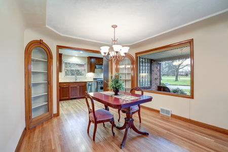 Open floor dining room with vintage table set, built in cabinets and light hardwood floor. Northwest, USA