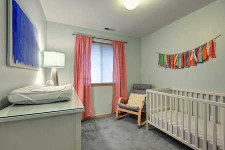 yellow walls: Nursery room features warm green walls, nursery crib, grey  chair with yellow pillow and red window curtains. Northwest, USA.  Stock Photo