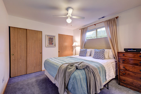 Restful white bedroom features king size bed with blue bedding, chest of drawers and two built-in closets. Northwest, USA